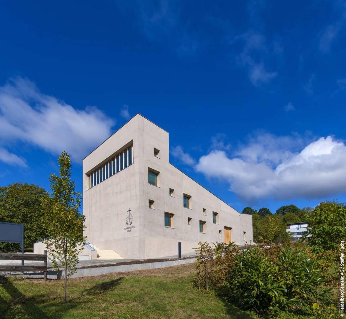 Der bemerkenswerte Kirchenbau sitzt am Rand eines Grünzugs und grenzt an Obstbaumwiesen. Bildquelle: HeidelbergCement AG / Steffen Fuchs