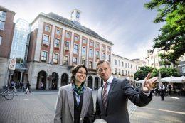 Zwei Personen vor einem Rathaus