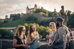 #wirfeiernbayern - Junge Menschen auf der Alten Mainbrücke in Würzburg, im Hintergrund die Festung Marienberg