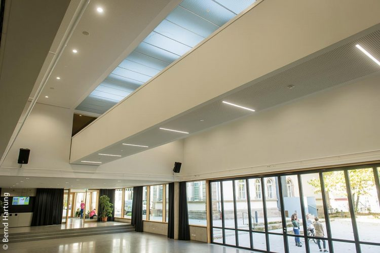 Eine Brücke verbindet im ersten Stock über der offenen Pausenhalle die beiden Gebäudeteile des Anbaus. Darüber befinden sich vier abgehängte Tageslichtelemente, die der Pausenhalle ein helles Ambiente verschaffen.