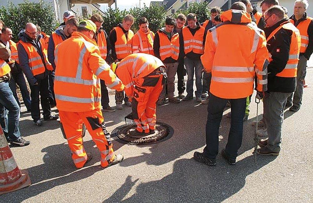 DWA-Kursteilnehmer verfolgen interessiert die Sanierungsarbeiten an einer Schachtabdeckung.