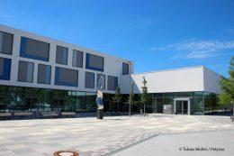 """Vor dem Eingang der neuen """"Eliteschule des Sports"""" im Münchner Stadtbezirk Milbertshofen-Am Hart lodert symbolisch eine Olympische Fackel – das Kunstwerk """"Feuer und Flamme"""" stammt von Bruno Wank aus München."""