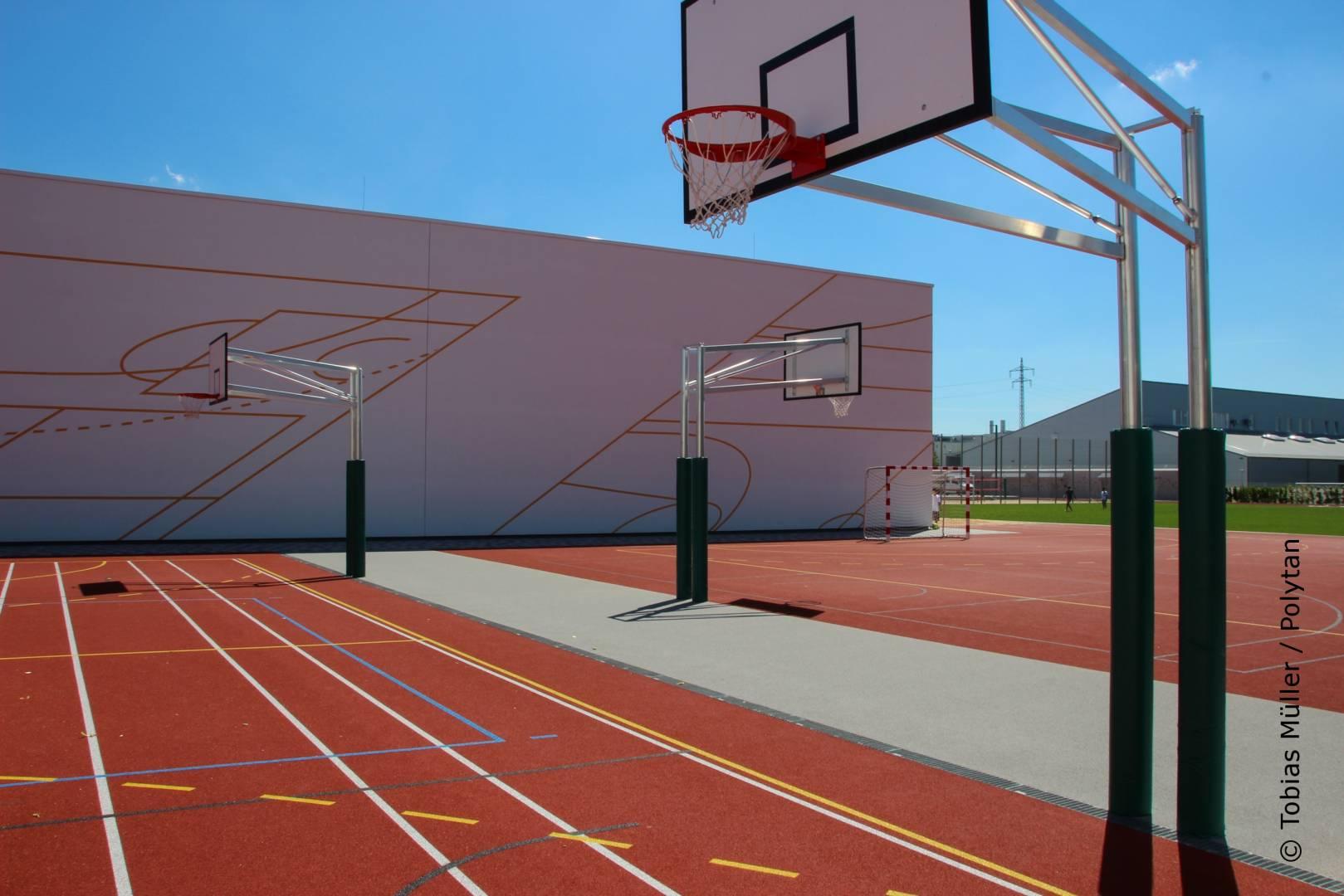 Zwei Basketballfelder ergänzen die Sportanlagen auf der Rückseite der Dreifachsporthalle. Als Kunststoffbelag entschieden sich die Planer für den wasserdurchlässigen PolyPlay S – ein universal einsetzbarer Sportboden mit glatter Oberfläche und einem sehr guten Ballsprungverhalten.