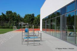 Der Fitness-Parcours vor der Sporthalle hat als Bodenbelag den Fallschutz PolyPlay FS erhalten – der hellgraue Boden von Polytan schützt die Sportler vor schweren Verletzungen und ist wasserdurchlässig.