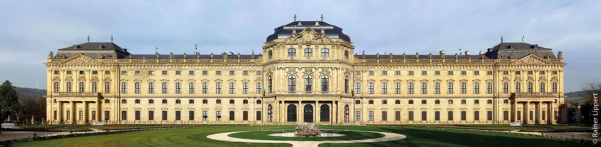 Blick vom Hofgarten aus auf die 168 Meter lange Gartenfront der Würzburger Residenz, die unter den Würzburger Fürstbischöfen von 1719 bis 1780 erbaut wurde. Sie gilt als der bedeutendste Residenzbau des Spätbarocks in Europa und wurde 1981 von der UNESCO zum Weltkulturerbe erklärt.