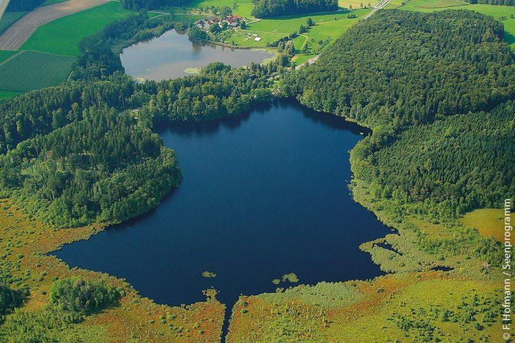 Der Häcklerweiher (großer See im Vordergrund) und der kleinere Buchsee (im Hintergrund) bei Fronreute im Landkreis Ravensburg liegen inmitten eines wertvollen Naturschutzgebietes. Zwischen beiden Seen verläuft die Bundesstraße 32.