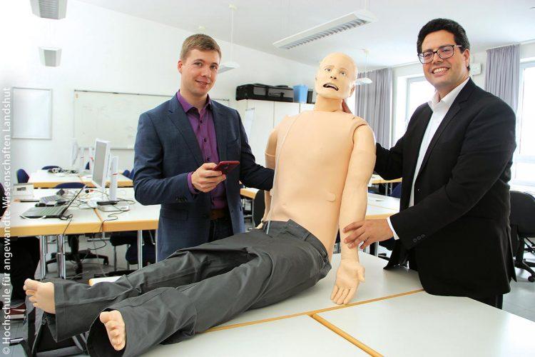 Prof. Dr. Abdelmajid Khelil (rechts) und IoT-Coach Tobias Piller arbeiten mit Studierenden der Hochschule Landshut an einer App, mit der ein Handy automatisch den Gesundheitszustand von Unfallopfern erkennt und Rettungskräften mitteilt – getestet wird an der lebensechten technischen Puppe. IoT
