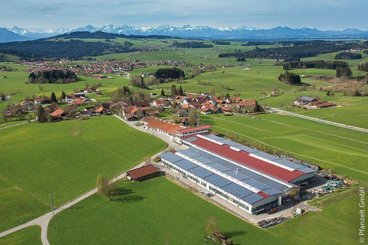 Der Blick auf die Allgäuer Hochalpen ist hier besonders imposant: Davor (links oben) liegt der Auerberg und davor ist die Gemeinde Rettenbach zu sehen, im Vordergrund der Rettenbacher Ortsteil Frankau mit den Gebäuden der Firma Pfanzelt (rechts vorne).