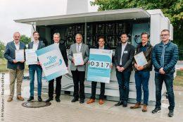 EnerPrax ist jetzt dabei! Dr. Heinrich Dornbusch (3.v.l.) überreichte den Beteiligten des Forschungsprojektes die Urkunde (v.l.): Wilfried Roos (Bürgermeister von Saerbeck), Nils Brücken (gwi), Prof. Dr. Christof Wetter, Christian Heinrich und Sebastian Nießen (beide FH Münster), Guido Wallraven (Projektmanager Klimakommune Saerbeck) und Lennart Lohaus (Praktikant Klimakommune). Hinter der Gruppe steht die frisch aufgebaute Redox-Flow-Batterie.