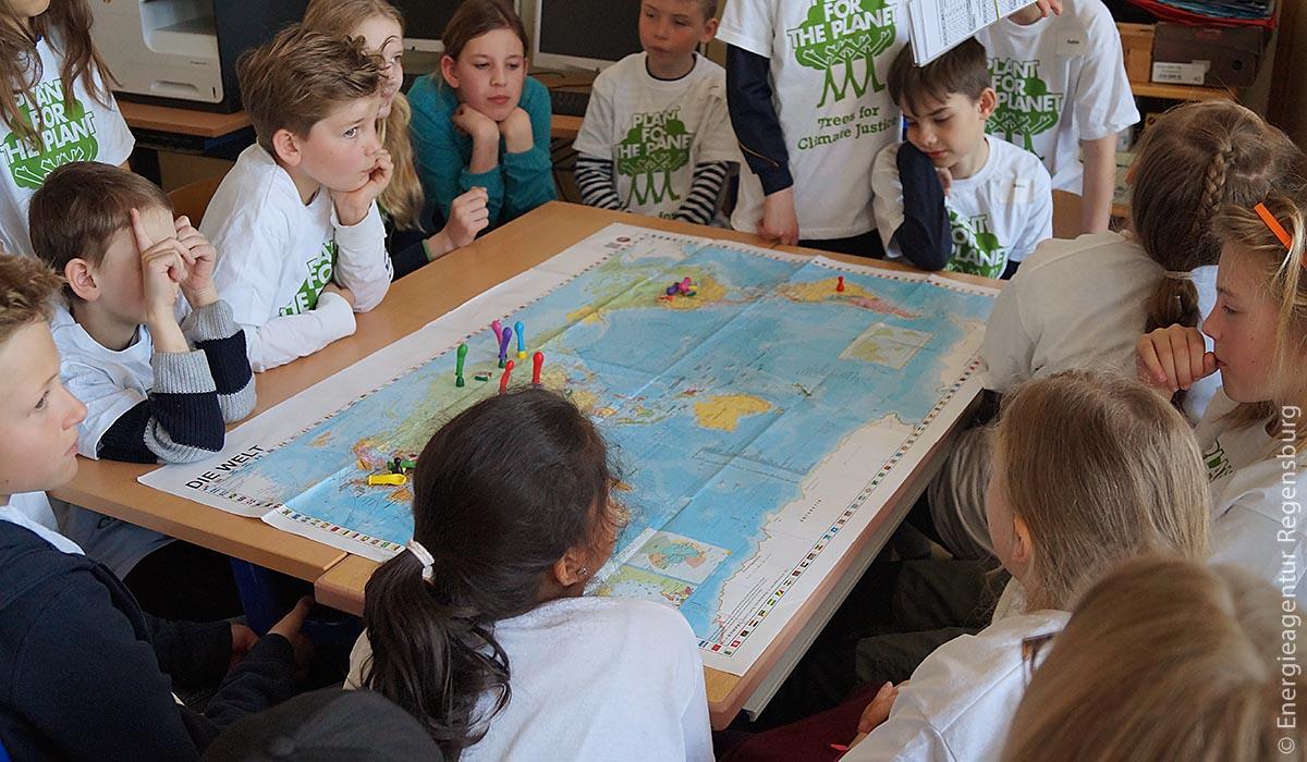 In mehreren Gruppen sprachen die Grundschüler über Klimagerechtigkeit und versuchten diese mit Hilfe von Spielfiguren und Luftballons auf einer Weltkarte sichtbar zu machen.
