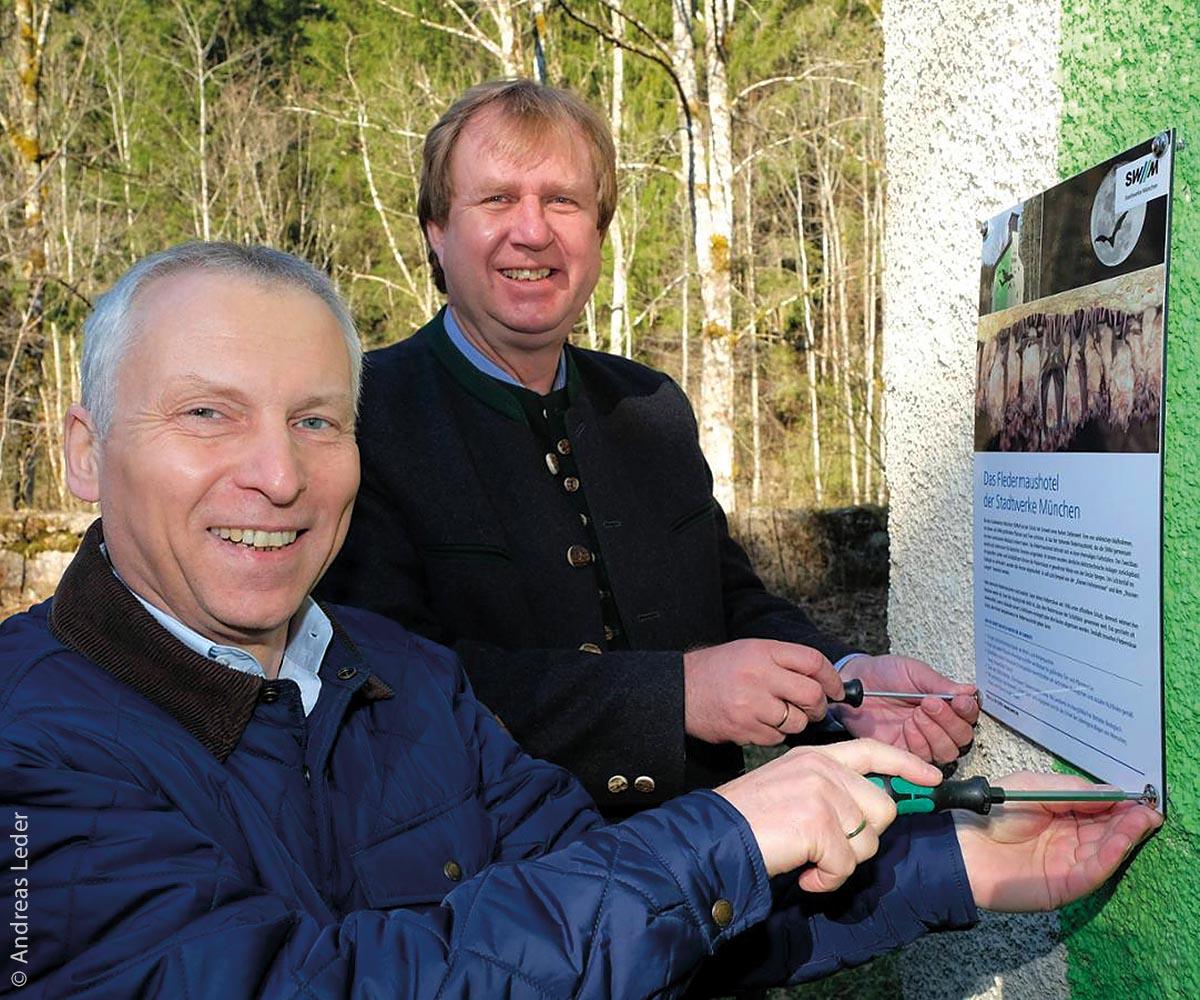 Helge-Uve Braun, Technischer Geschäftsführer der SWM (links), und Miesbachs Landrat Wolfgang Rzehak bringen ein Informationsschild über das neue Fledermaushotel Neumühle an der Fassade an.