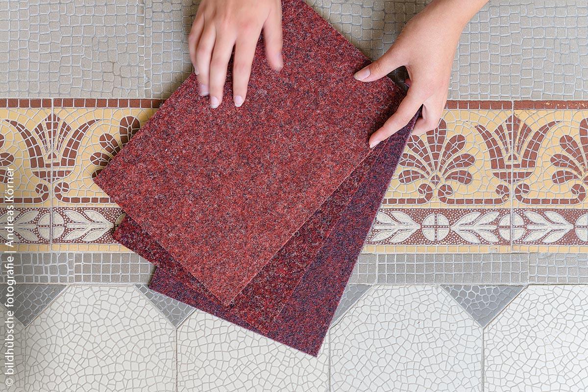 Der Nadelvlies-Teppich von FINDEISEN greift die rot-graue Farbkombination der historischen Fliesen im Treppenhaus des 1901/1902 erbauten Gebäudes auf, in dem heute die VHS Ettlingen untergebracht ist.