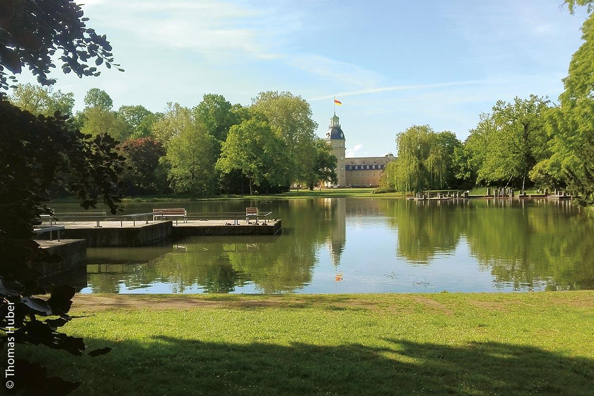 Blick zum Schloss über den See des Parks: Das Areal des Schlosses in Karlsruhe ist eine riesige Parkanlage. Man benötigt viel Zeit, um es zu durchwandern.