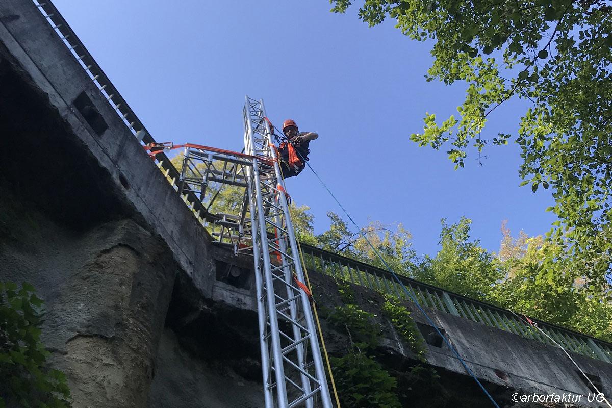 Das Bild zeigt einen Feuerwehrmann der einen Absturzsicherungskurs durchführt und gerade eine Brücke mit einer Gerüstleiter erklettert.