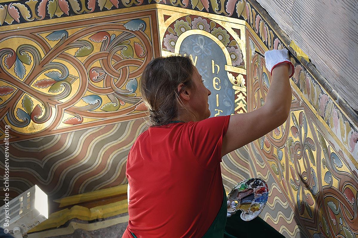 Eine von mehreren Restauratorinnen kümmert sich um die kunstvoll gestalteten Wandmalereien: Augenmaß und eine ruhige Hand sind für Restauratoren unerlässliche Fähigkeiten.