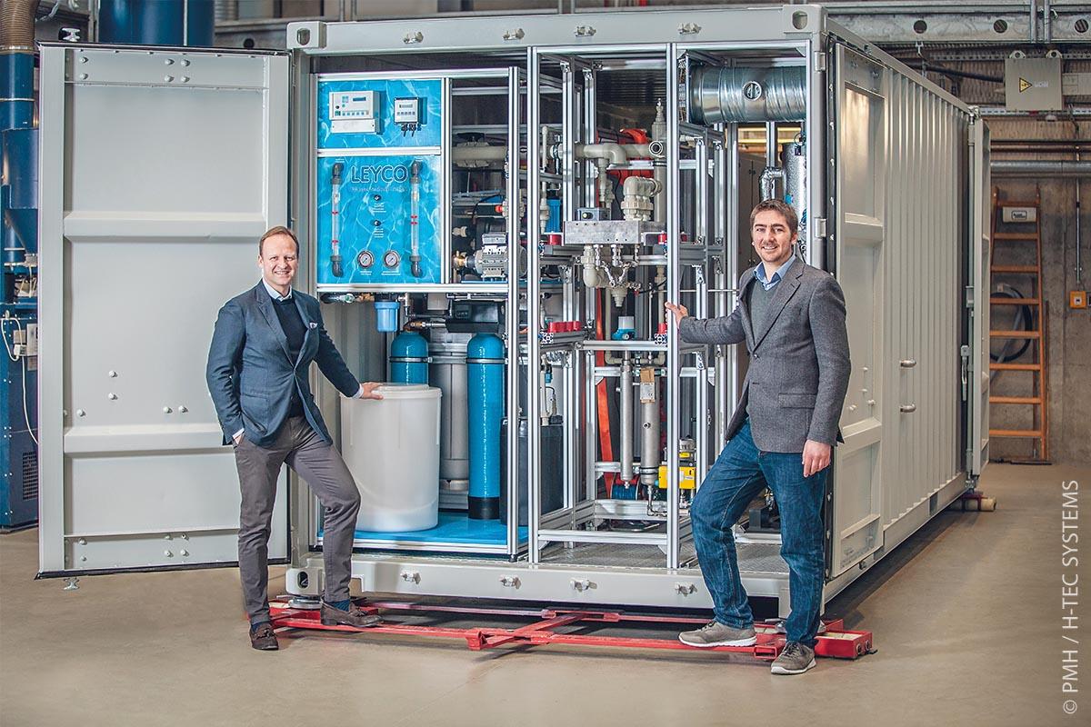 Die PEM-Elektrolyseure für eFarm werden am Standort Augsburg zur standort-flexiblen Container-Lösung montiert (von links: Geschäftsführer Frank Zimmermann und Dr. Joachim Herrmann).