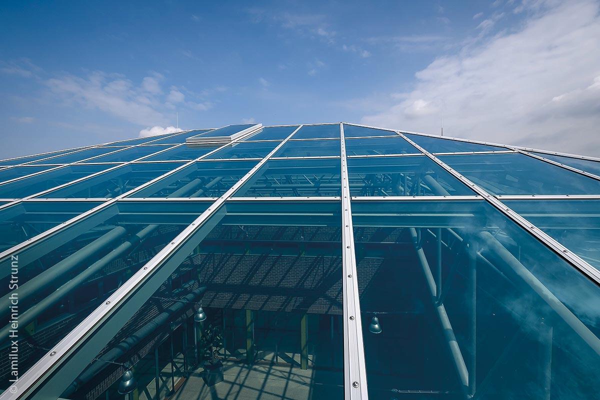 Die gläserne Dachfläche umfasst insgesamt 275 Quadratmeter und ist zweifach isolierverglast. Das neue Glasdach überzeugt funktional durch ein optimiertes Dichtungs- und Entwässerungssystem und reduziert Wärmeverluste in der Rahmenkonstruktion. Das Atrium des Gymnasiums ist nun mit Tageslicht durchflutet.
