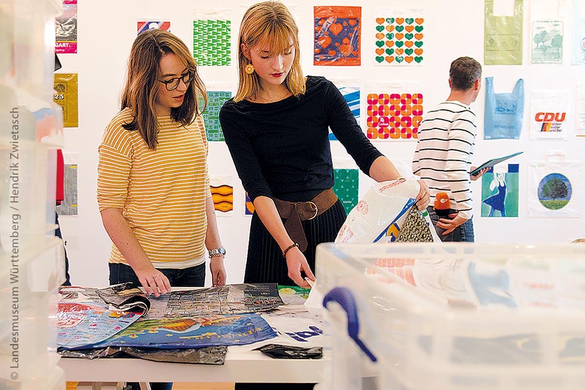 In der Sonderausstellung sind die Plastiktüten als Exponate nicht nur an den Wänden angebracht, sondern auch auf Tischen ausgelegt. Auch die gestapelten Kisten mit einer riesigen Menge weiterer Plastiktüten sind Teil der Ausstellung.
