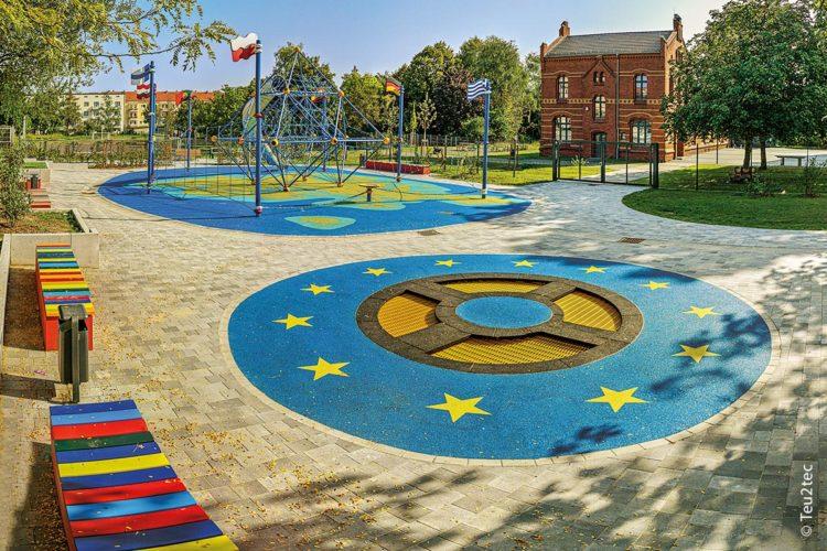 Auf dem Spielplatz der Nationen in Magdeburg gibt es auch ein rundes Trampolin (Vordergrund), das in Blau von der Flagge Europas mit den zwölf Sternen umrahmt wird.