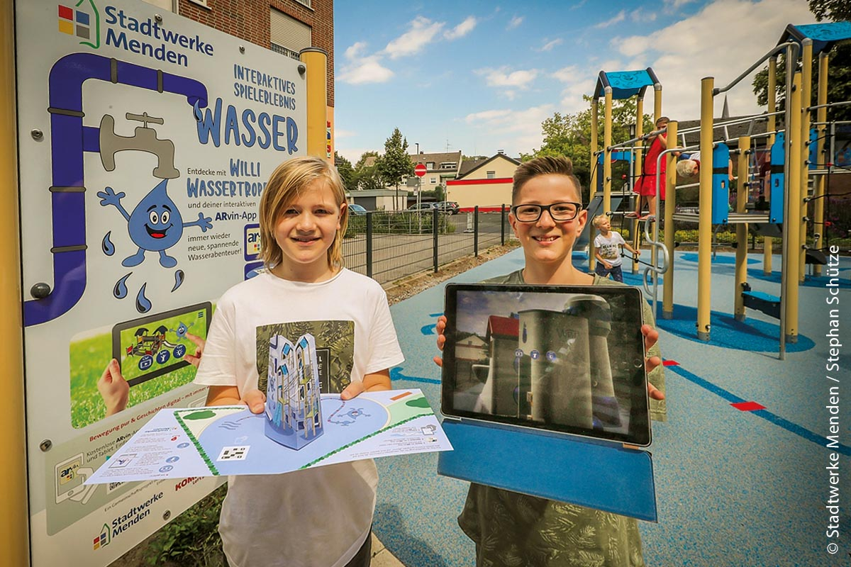 Juris (links) präsentiert die Pop-up-Karte, die digitale Erlebnisse mit Willi, dem Wassertropfen, zu Hause oder im Schulunterricht ermöglicht. Fyn zeigt eine Ansicht der interaktiven Spielfläche auf dem Tablet.