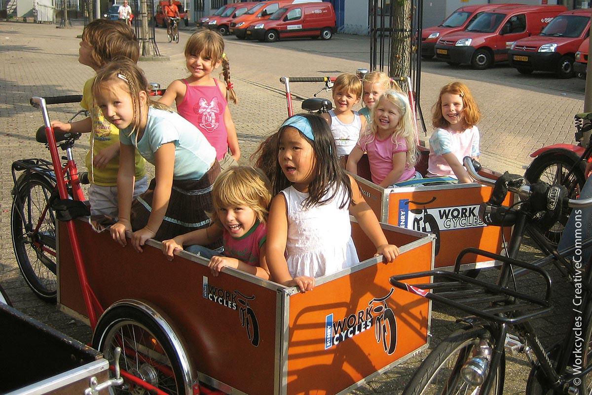"""In den Städten der Niederlande – wie in diesem Beispiel mit lebendiger """"Fracht"""" in Amsterdam – gehören Lastenräder schon viele Jahre zum gewohnten Bild."""