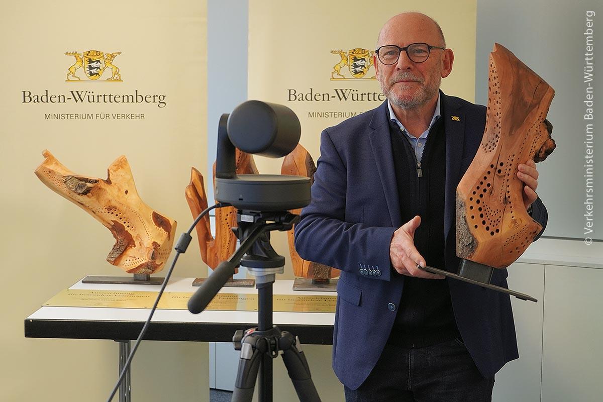 Winfried Hermann, Verkehrsminister von Baden-Württemberg, übergibt den Gewinnern Hartholz-Skulpturen als Preise.