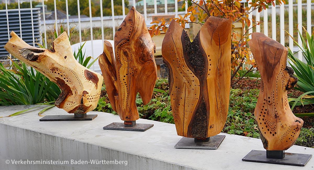 """Als Dank erhielten die prämierten Stadt- und Landkreise Hartholz-Skulpturen des Schweizer Künstlers Marcel E. Plüss. Die sogenannte """"Wildbienenkunst"""" sieht nicht nur schön aus, sondern bietet mit den gebohrten Hohlräumen auch Wildbienen ein Zuhause. Die Preise von links: für den Rhein-Neckar-Kreis, den Ostalbkreis, für den Rems-Murr-Kreis und ganz rechts der Preis für Freiburg."""
