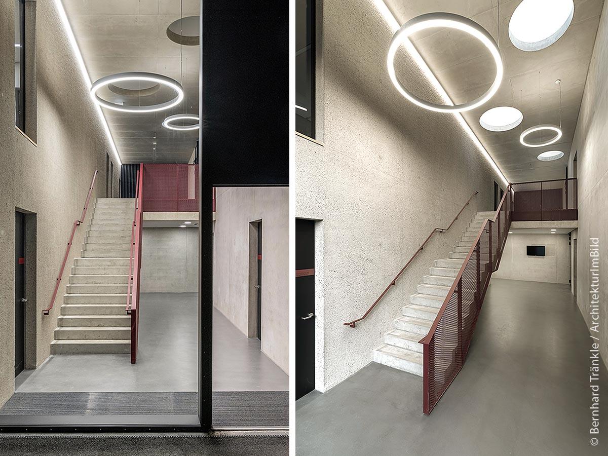 Der Eingangsbereich des Feuerwehrhauses in Kaufbeuren mit Foyer: Natürliches Licht erhält man über kreisrunde Dachfenster, deren Form durch die ringförmigen Leuchten aufgegriffen wird.